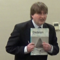 Photograph of Paul Salvidge leaning forward as he gives a speech and pointing to a book called DADAISM