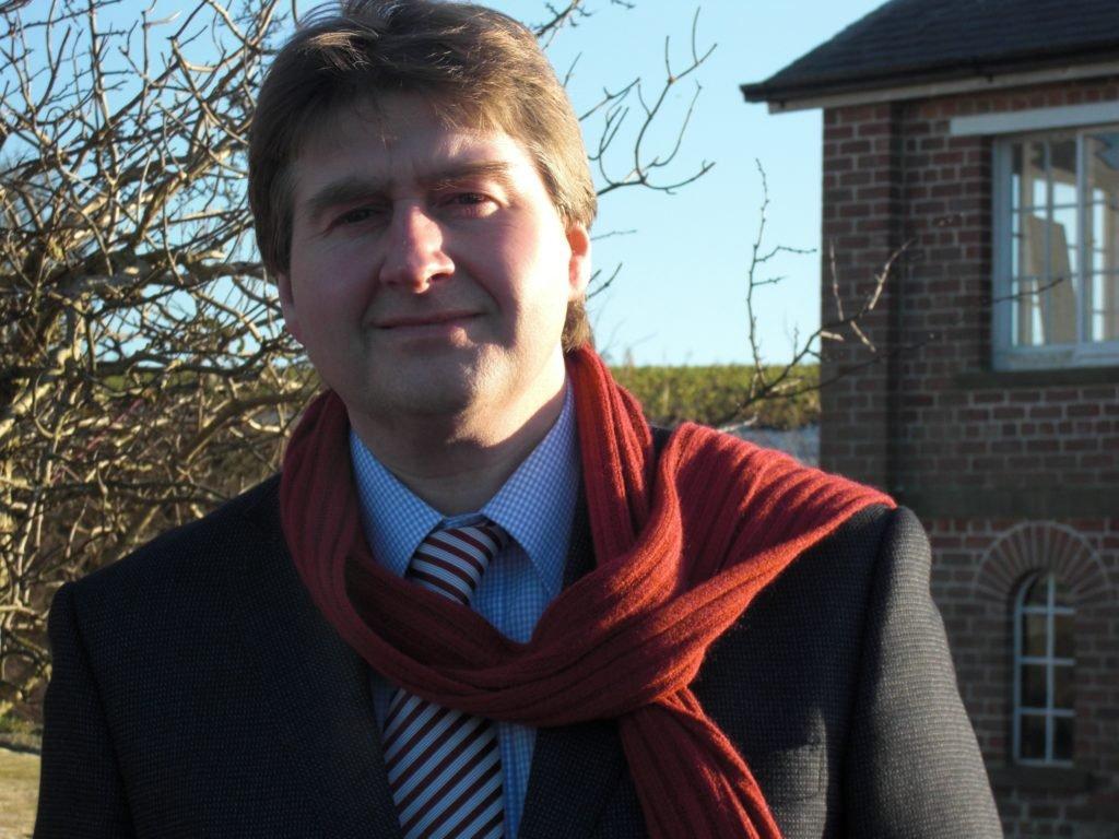 Paul Salvidge wearing jacket, tie and maroon scarf
