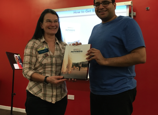Photograph of Clare handing Murali a Pathways Programme Package